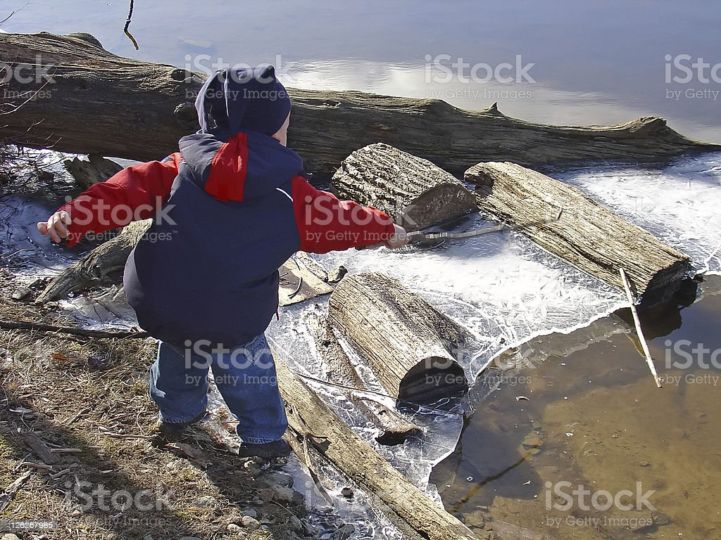 Boy/child is playing at an icy winter lake royalty-free stock photo