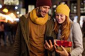 Boyfriend and girlfriend looking at smartphone