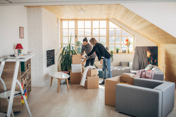 Boyfriend and girlfriend unpacking boxes in new home Man and woman, young couple moving into their new apartment together. renting stock pictures, royalty-free photos & images
