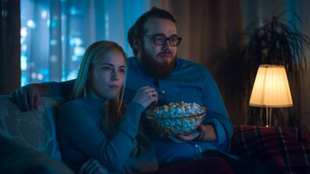 novio y novia viendo tv. se sientan en un sofá en su acogedora sala de estar y comen palomitas de maíz. es la noche. - sequence animation fotografías e imágenes de stock
