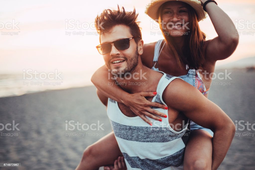 Boyfriend carrying girl on his back stock photo