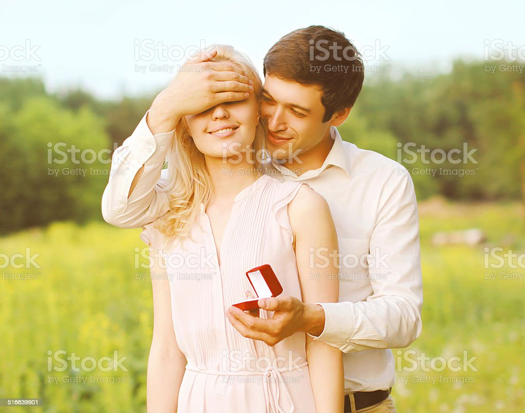 Boyfriend closed his eyes a girl, making a surprise ring stock photo