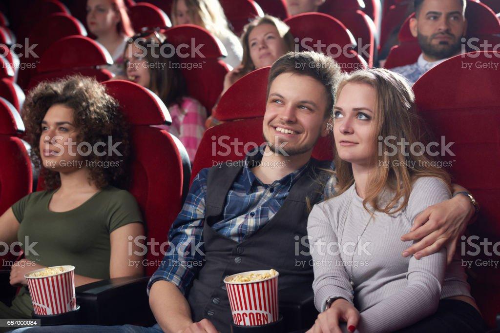 Freund umarmt seine hübsche Freundin im Kino. Lizenzfreies stock-foto