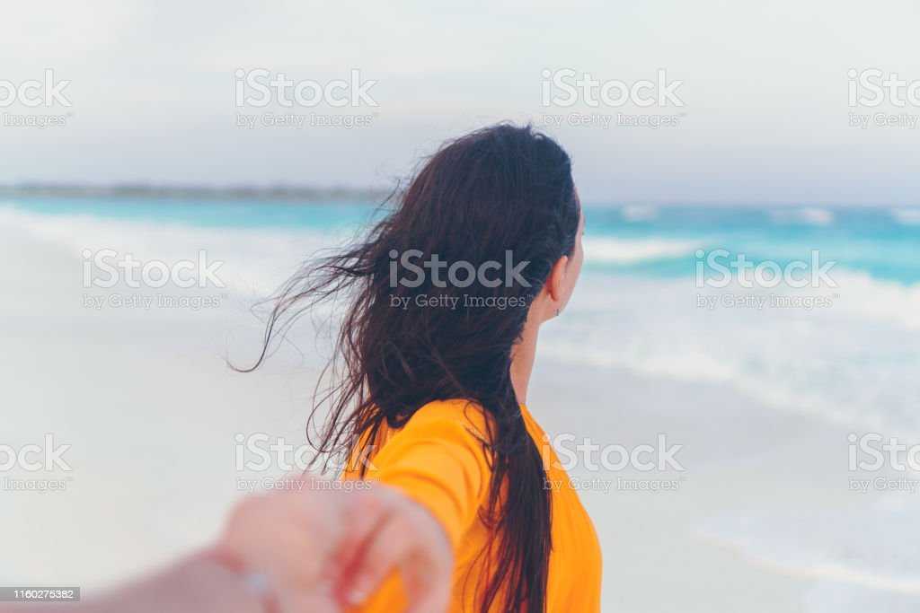 Boyfriend following girlfriend holding hands on white wild beach laughing and smiling Follow me. Portrait of woman with long hair. Boyfriend following girlfriend holding hands on white wild beach laughing and smiling Back Stock Photo