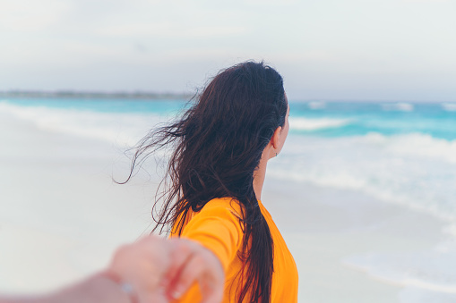 Boyfriend Following Girlfriend Holding Hands On White Wild Beach Laughing And Smiling Stock Photo - Download Image Now