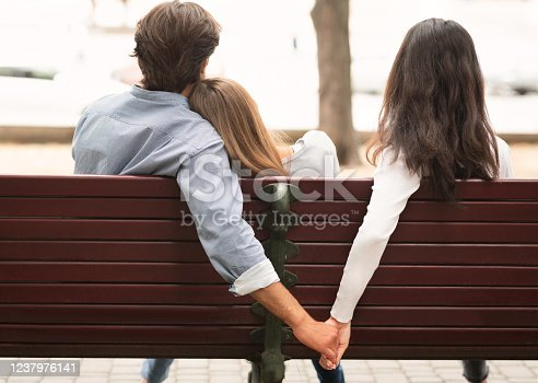 Love Triangle. Cheating Boyfriend Hugging Girlfriend Holding Hands With Her Girl Friend Sitting On Bench Together In Park Outdoor. Back-View