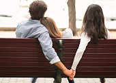 istock Boyfriend Holding Hands With Girlfriend's Friend Sitting On Bench Outdoor 1237976141