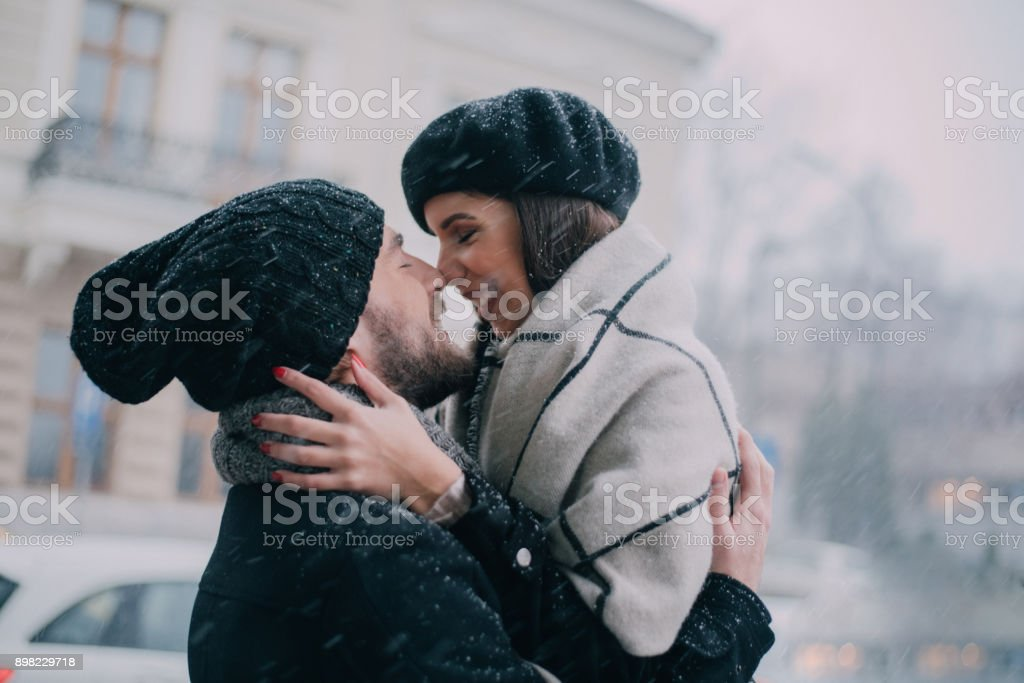 Boyfriend holding his girlfriend in arms and kissing her stock photo