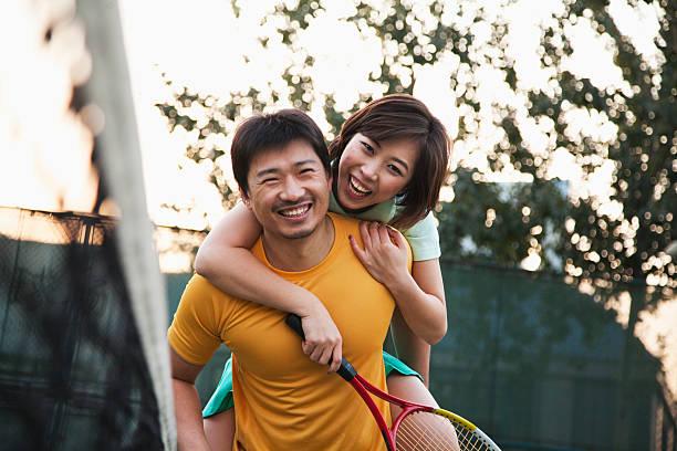 boyfriend holding his girlfriend next to the tennis net - 30 39 jaar stockfoto's en -beelden