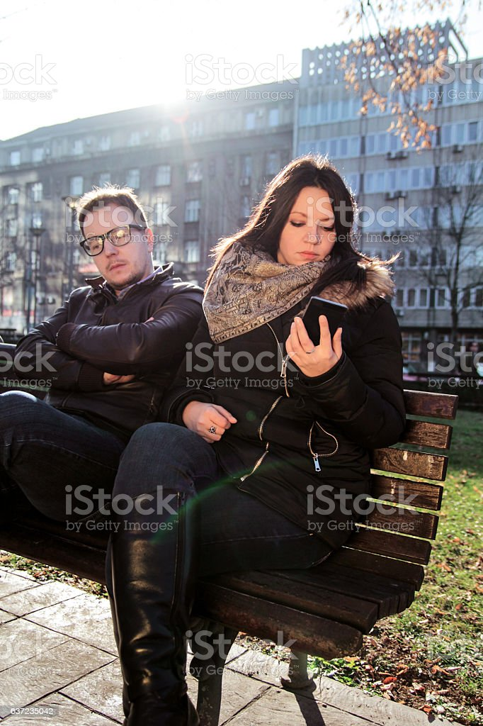 Boyfriend is bored and woman using a smartphone stock photo