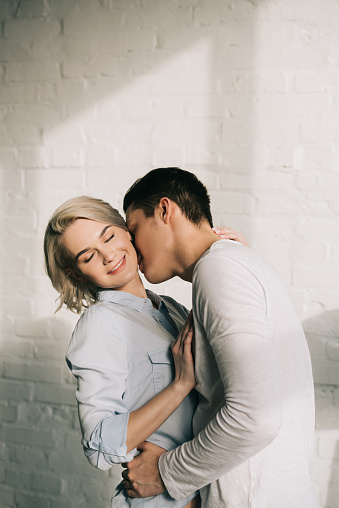 Boyfriend Kissing Girlfriends Neck At Home Stock Photo