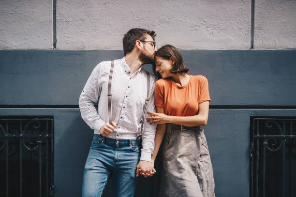Boyfriend kissing his girlfriend by the wall. stock photo