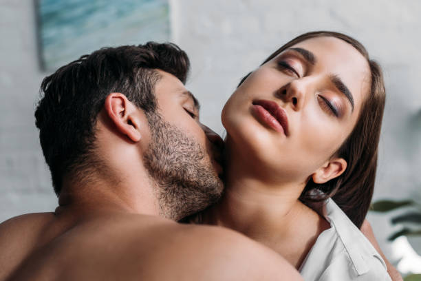 boyfriend kissing sensual girlfriends neck in bedroom in morning - kissing on neck stock photos and pictures