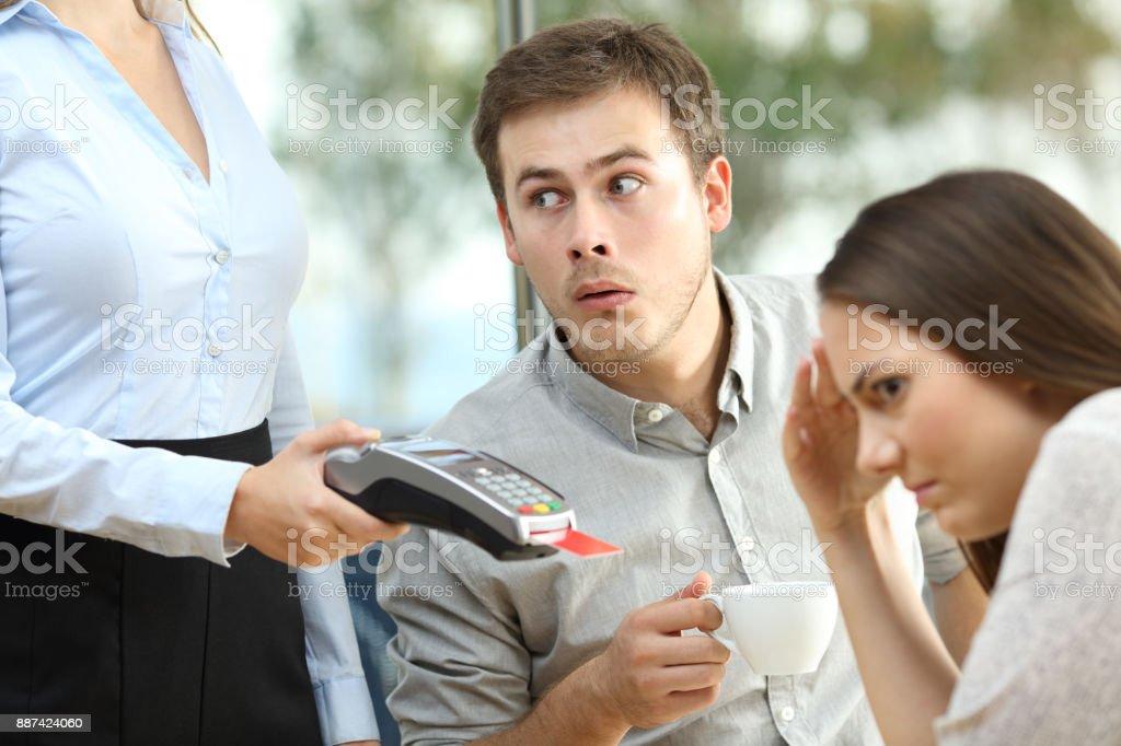 Boyfriend looking at waiter chest stock photo