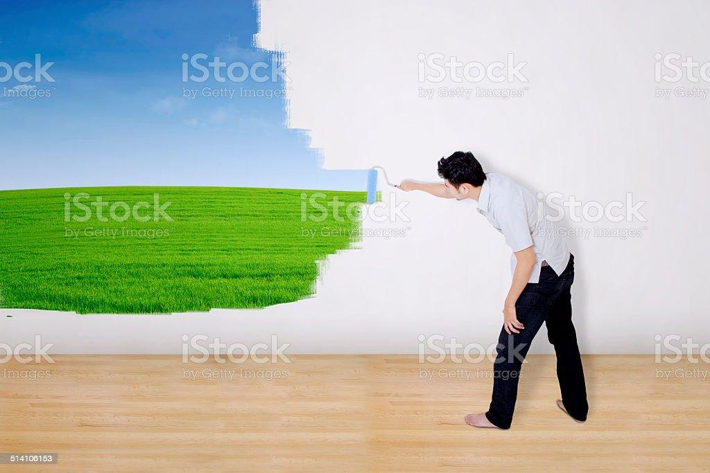 Boyfriend painting green field on wall stock photo