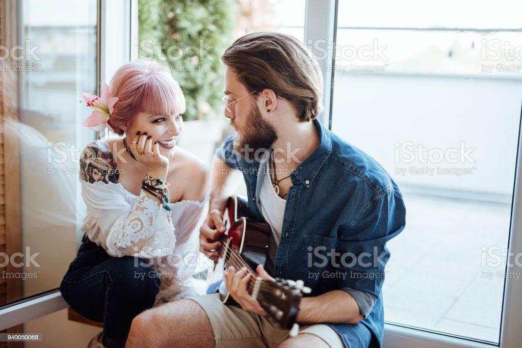 Namorado tocando guitarra com a namorada - foto de acervo