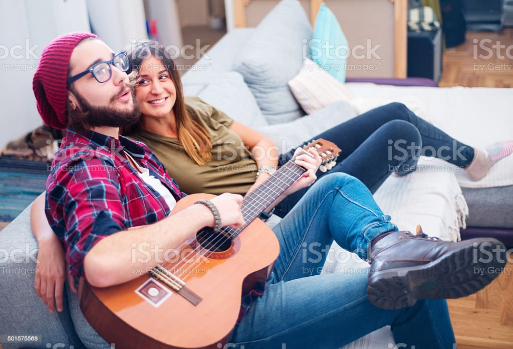 boyfriend playing to his girlfriend stock photo