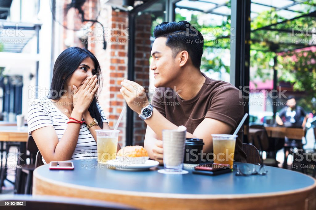 Boyfriend proposing his girlfriend at a cafe stock photo