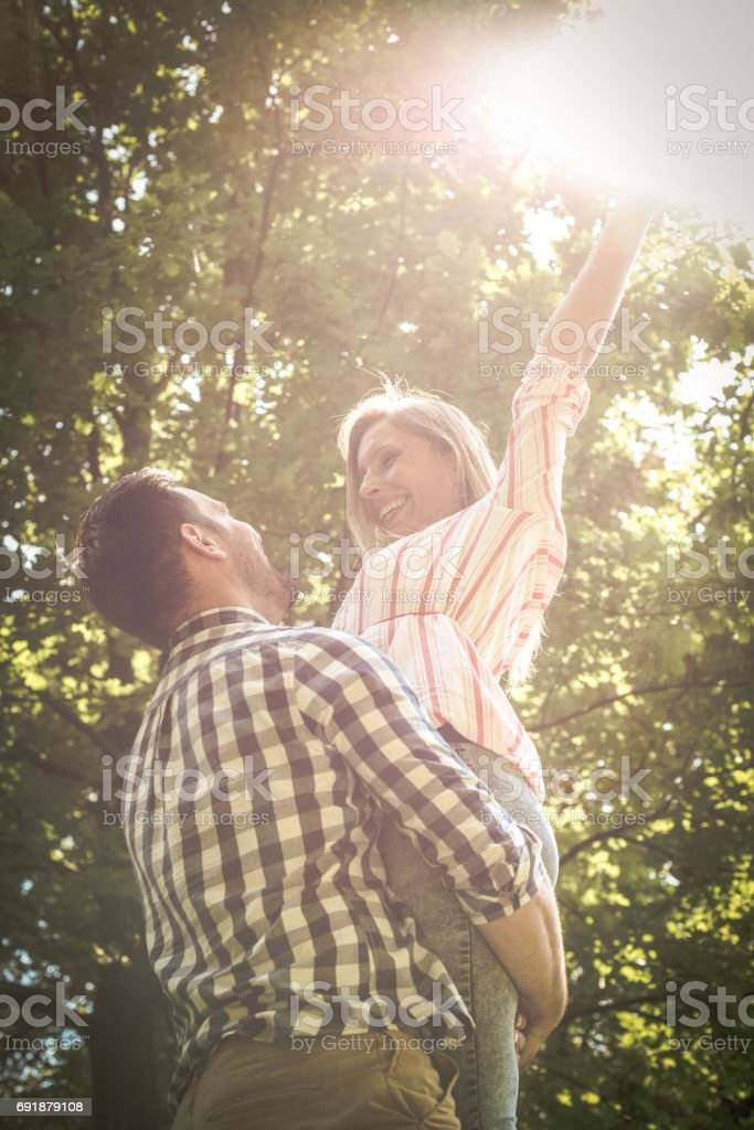 Boyfriend rises the girl in height. Young couple enjoying in summer day. stock photo