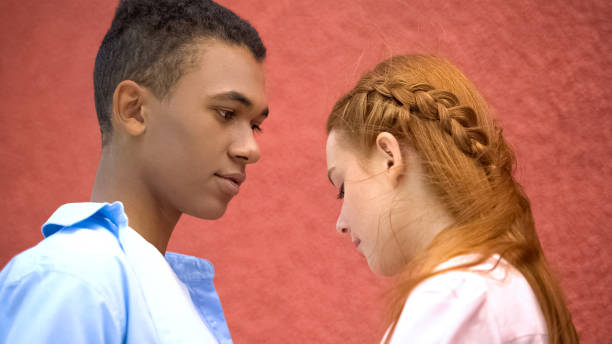 boyfriend talking to beautiful shy girlfriend, tender moment, first relations - kids kiss embarrassed foto e immagini stock