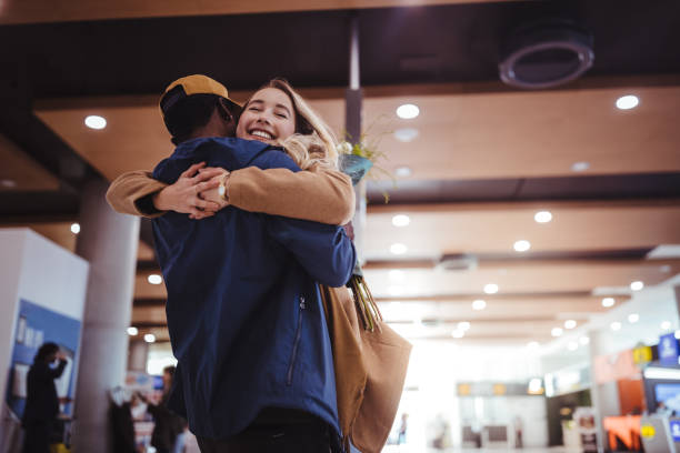 Boyfriend welcoming and embracing excited girlfriend at airport stock photo