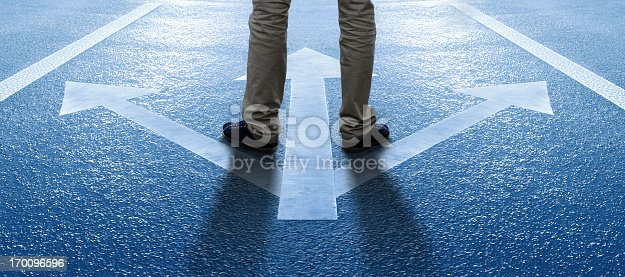 Man standing on arrows painted on asphalt. Bright light in background.