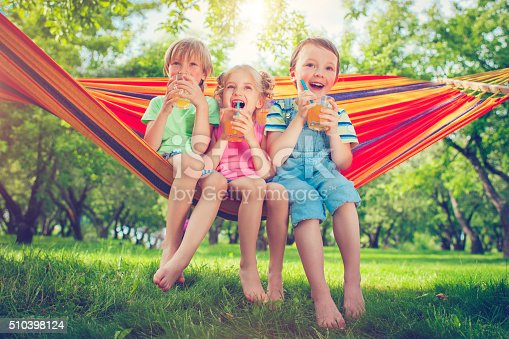 Three happy children drinking lemonade  in hammock in a park or back yard in summer