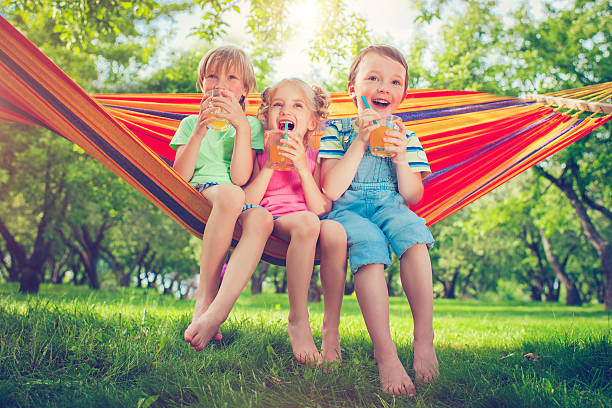 boys and girl in summer - drinking juice stock photos and pictures