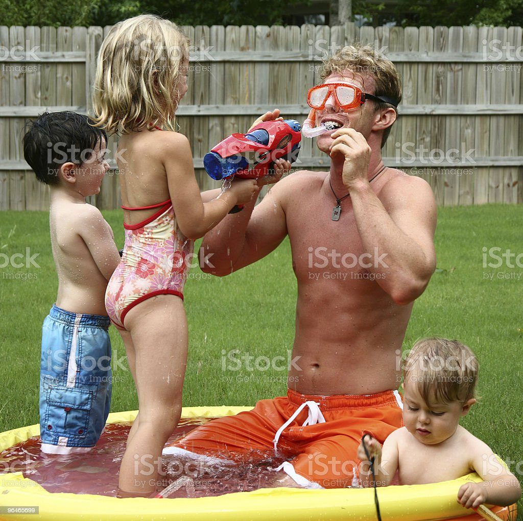Boys and girl play with dad in the kids pool royalty-free stock photo