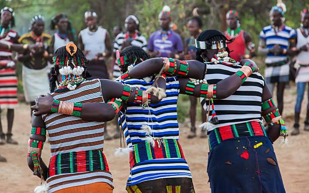 jungen und mädchen in der traditionellen evangaty zeremonie.   turmi, äthiopien. - lange gestreifte röcke stock-fotos und bilder