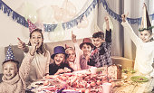 Boys and girls behaving jokingly during friend's birthday party