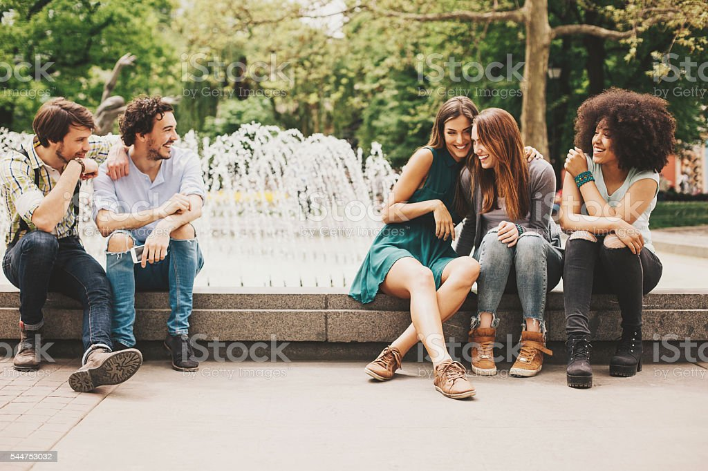 Boys and girls flirting in the park stock photo