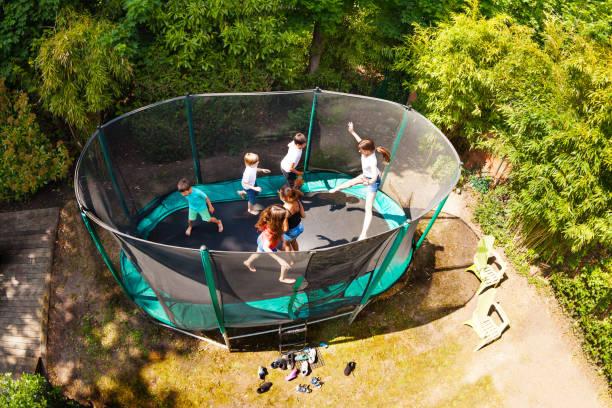 jungen und mädchen springen auf dem trampolin im garten - gartentrampolin stock-fotos und bilder
