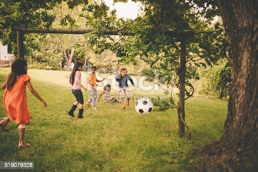 621475196 istock photo Boys and girls playing soccer in a lush green park 519079328