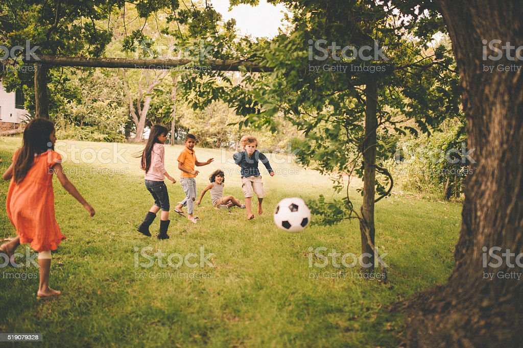 Boys and girls playing soccer in a lush green park stock photo