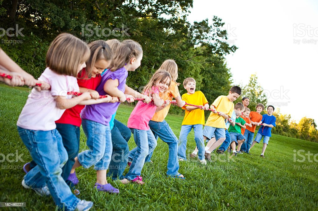 Boys and girls playing tug-of-war on the grass royalty-free stock photo