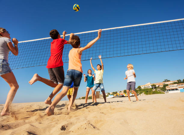 Boys and girls playing volleyball on the beach stock photo