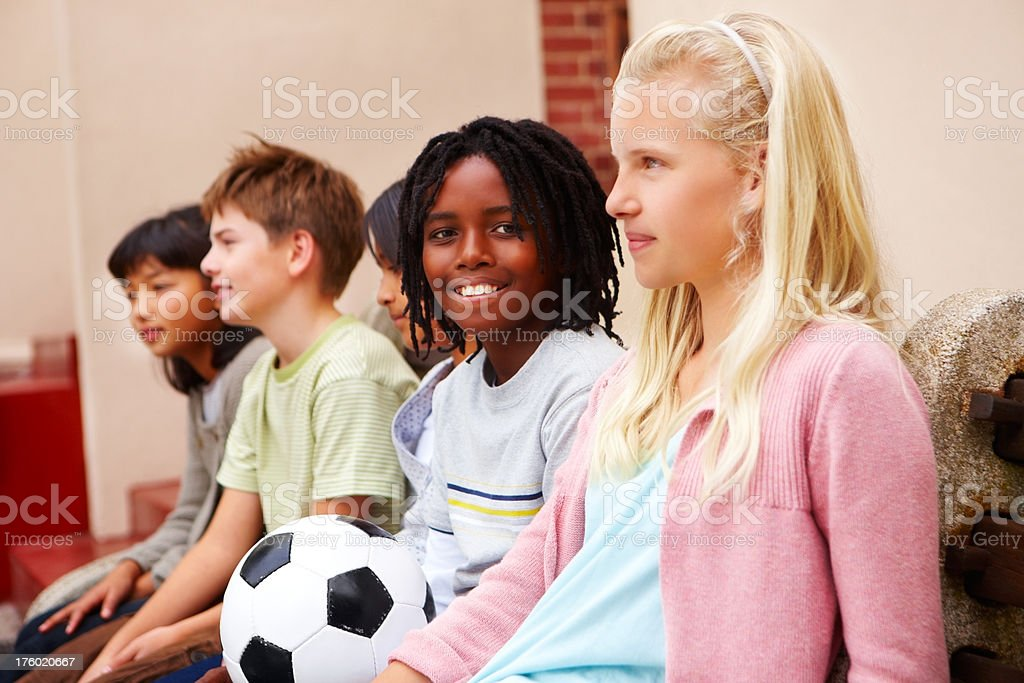 Boys and girls sitting with a football royalty-free stock photo