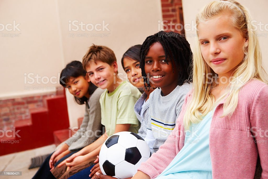 Boys and girls sitting with football royalty-free stock photo