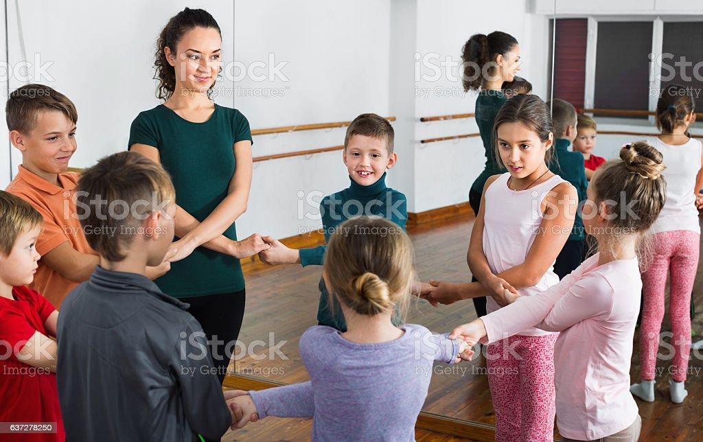 Boys and girls studying folk dance in studio - Photo