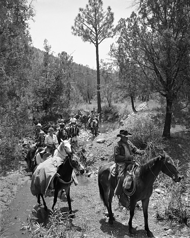 Tucson, Arizona, USA - August 15, 1950: Guides with tent and other equipment on a donkey lead boys on an overnight trail ride near Tucson.