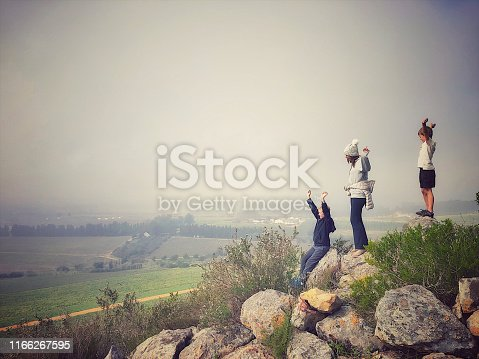 Side view of two boys and mother arms raised standing on a rocky hill overlooking a farm below in the Cape Winelands Cape Town South Africa