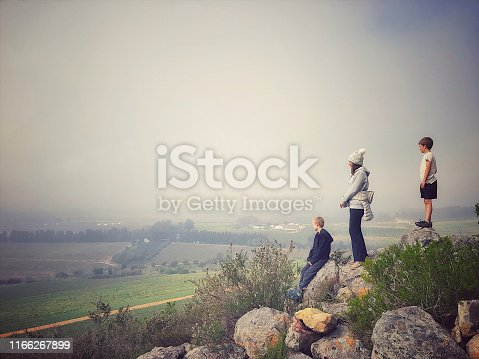 Side view of two boys and mother standing on a rocky hill overlooking a farm below in the Cape Winelands Cape Town South Africa