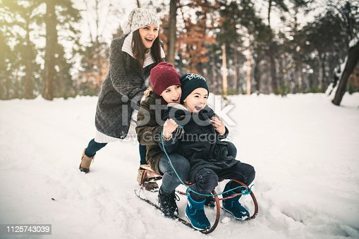 Boys and Mum On A Sled Playing In The Snow In Winter
