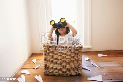 A little boy playing with paper airplanes while sitting in a basket
