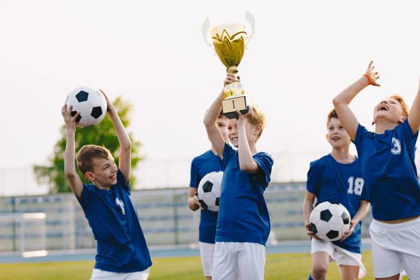 jongens zijn juichen voor hun team overwinning. gelukkige kinderen vieren succes in de sport jeugdtoernooi. boys holding gouden beker. voetbalschool toernooi voor kinderen - sportkampioenschap stockfoto's en -beelden