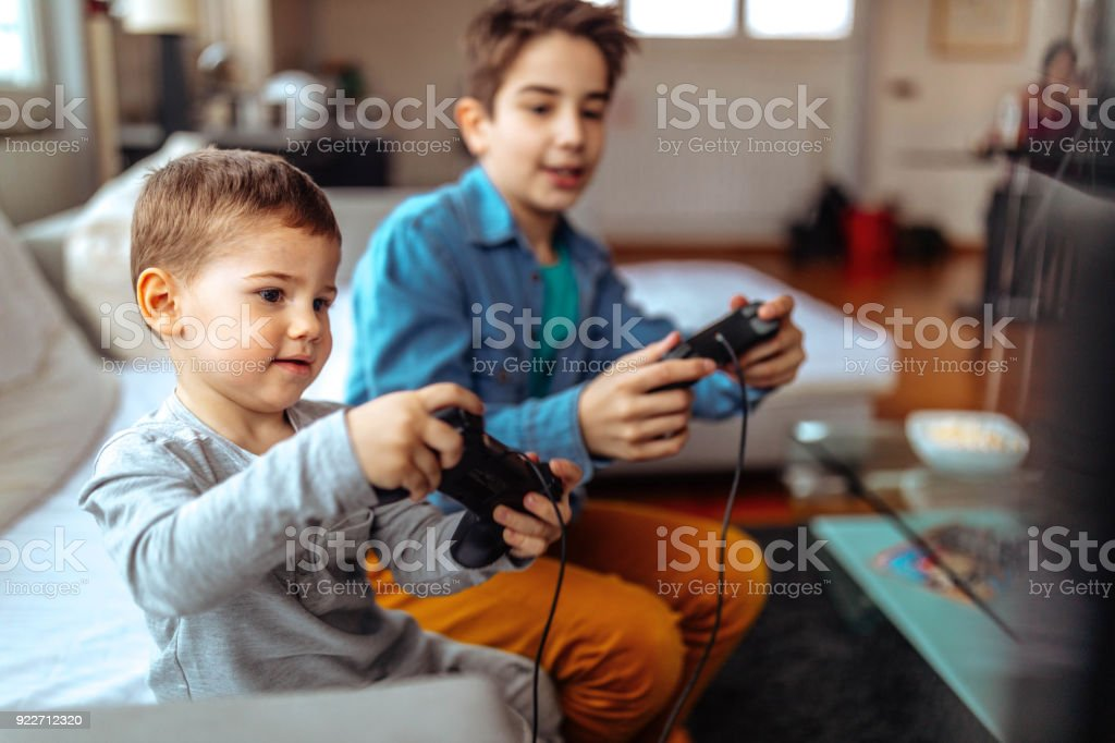 Boys are having fun Photo children playing with video games at home Adult Stock Photo