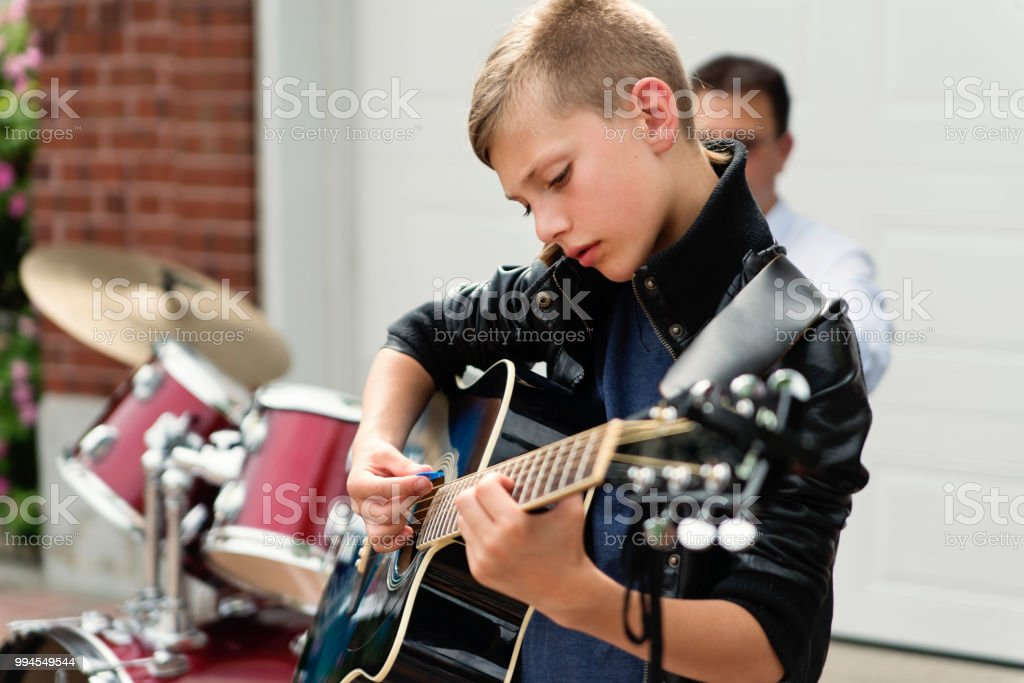 Boy's band getting ready to play in family driveway. stock photo
