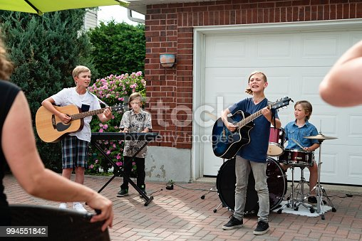 Garage band of young boys between 9 and 12 year's old, two pairs of brothers, playing in front of family and friends in suburb home driveway on a hot summer day. Horizontal outdoor's full length shot with copy space.