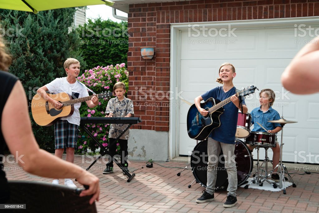 Boy's band in concert in family driveway in summer. stock photo
